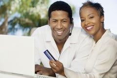 Par med kreditkorten och hörlurar med mikrofon som gör online-shopping Royaltyfri Foto