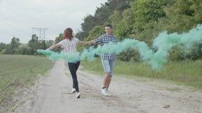 Par med kulör rök som cirklar på den dammiga vägen