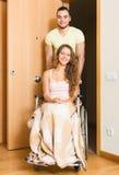 Par med kvinnan i rullstol nära dörr Royaltyfri Foto