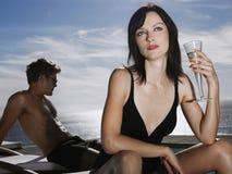 Par med kvinnan som rymmer Champagne Glass By Sea Royaltyfria Foton