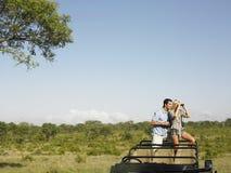 Par med kvinnan som ser till och med kikare i jeep  Royaltyfri Foto