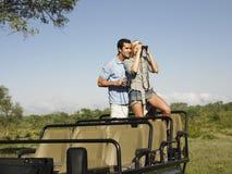 Par med kvinnan som ser till och med kikare i jeep  Arkivfoto
