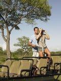 Par med kvinnan som ser till och med kikare i jeep  Fotografering för Bildbyråer