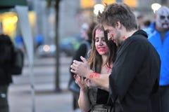 Par med levande dödframsidan målar att se deras telefon på squaen royaltyfria bilder