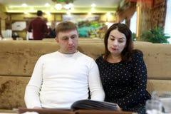 Par med menyn på soffan royaltyfria foton