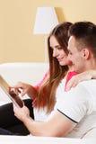 Par med minnestavlasammanträde på soffan hemma Arkivfoto