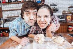 Par med mjöl på framsidor som knådar deg Arkivbild