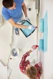 Par med målarfärgrullar som hemma målar väggen Arkivfoto