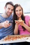Par med pizza och TVfjärrkontrollen Royaltyfri Foto