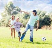 Par med pojken som spelar med fotbollbollen Arkivfoto