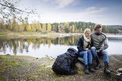Par med ryggsäcken som kopplar av på Lakeshore under att campa Arkivfoton