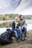 Par med ryggsäcken som kopplar av på Lakeshore under att campa Royaltyfria Foton