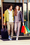 Par med shoppingpåsar och resväskan går ut flygplatsen royaltyfri foto