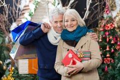 Par med shoppingpåsar och gåva på jul Arkivbild