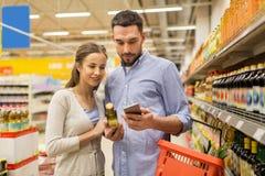 Par med smartphoneköpandeolivolja på livsmedelsbutiken royaltyfri foto