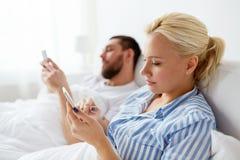 Par med smartphones i säng hemma Arkivbilder