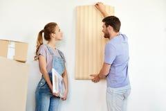Par med tapeten som reparerar lägenheten eller hemmet Arkivfoto