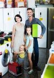 Par med två ungar som rymmer asken med ny elektronik royaltyfri bild