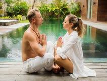 Par mediterar tillsammans i morgonen arkivfoto