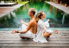 Par mediterar tillsammans vid pölen royaltyfri foto