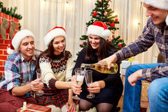 Par nouvelle année par groupe d'amis dans des chapeaux de Santa Claus verse Photos libres de droits