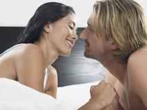 Par omkring som ska kyssas på säng Arkivbilder
