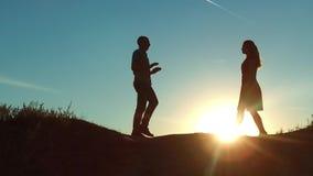 Par på att krama för solnedgångkonturkyss ultrarapidvideo Barnet kopplar ihop att kyssa på solnedgången man- och flickamöte varje lager videofilmer