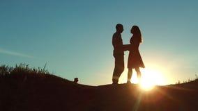 Par på att krama för solnedgångkonturkyss ultrarapidvideo Barnet kopplar ihop att kyssa på solnedgången man- och flickamöte varje stock video