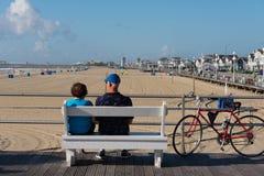 Par på bänk på strandpromenaden Arkivfoto