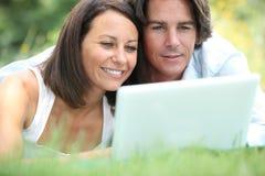 Par på bärbara datorn Fotografering för Bildbyråer