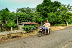 Par på en motorisk cykel på en grusväg Royaltyfri Bild