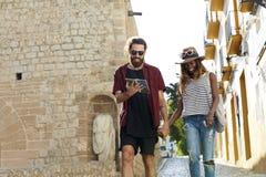 Par på ferie går och att läsa en resehandbok, tre fjärdedelar arkivfoto