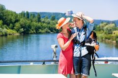 Par på floden kryssar omkring bärande solhattar i sommar royaltyfri foto