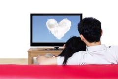 Par på hållande ögonen på förälskelse för röd soffa att fördunkla på tv Royaltyfri Bild