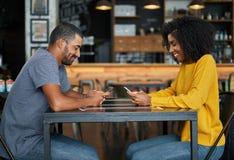 Par på kafétabellen genom att använda mobiltelefoner royaltyfria bilder