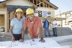 Par på konstruktionsplatsen med ritningen Royaltyfria Foton