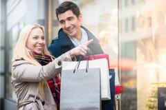 Par på shoppar fönstret som gör att shoppa för jul Arkivbild