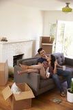 Par på Sofa Taking ett avbrott från uppackning på rörande dag Arkivfoto
