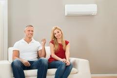 Par på Sofa Using Air Conditioner Royaltyfri Fotografi