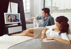 Par på soffan med TVfjärrkontrollen Arkivfoton