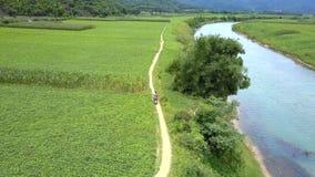 Par på sparkcykelritter mellan floden och jordnötfältet arkivfilmer