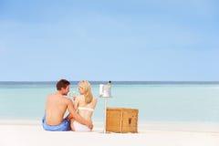 Par på stranden med lyxiga Champagne Picnic Arkivbilder
