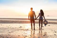 Par på stranden på solnedgångsommarsemestern, härligt ungdomarförälskat gå, händer för mankvinnainnehav arkivfoton