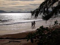 Par på stranden på solnedgångbakgrund royaltyfri bild