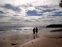 Par på stranden på solnedgångbakgrund arkivfoto