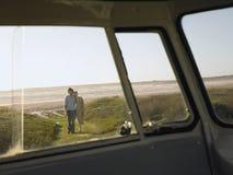 Par på stranden som går in mot Campervan Fotografering för Bildbyråer