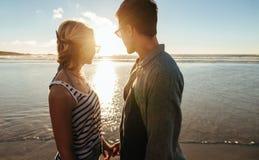 Par på stranden som ser solnedgången royaltyfri bild
