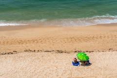 Par på stranden under solslags solskydd Arkivfoto