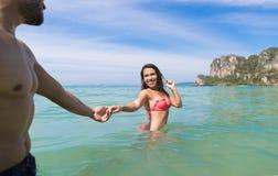 Par på strandsommarsemester, ungdomari vatten, för manhand för kvinna hållande hav för hav Royaltyfri Bild