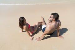 Par på strandsommarsemester, ungdomarsom sitter på sand, hav för mankvinnahav Arkivfoto
